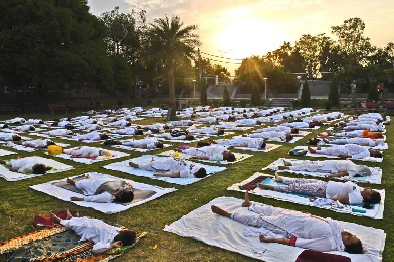 Pessoas estão deitadas no chão, lado a lado, respeitando certo distanciamento, durante a atividade