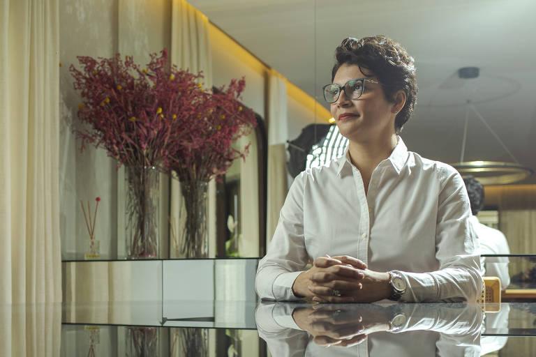Mulher de perfil, veste camisa branca, tem cabelos curtos, está sentada a uma mesa espelhada na qual é possível ver seu reflexo. Ao fundo ambiente que parece ser de uma sala de estar.
