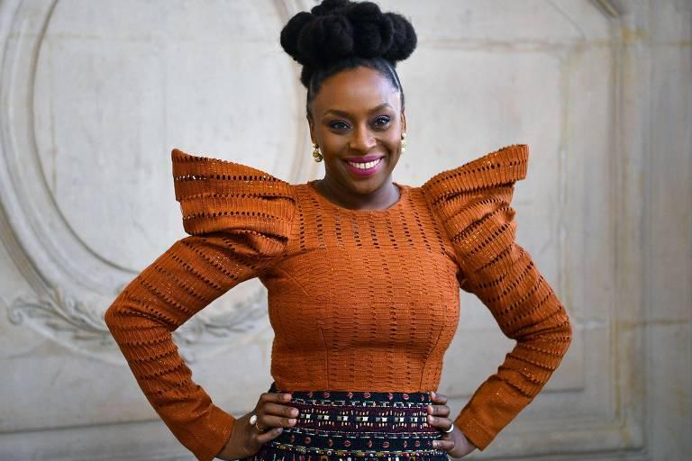 mulher negra sorrindo com mãos apoiada na cintura
