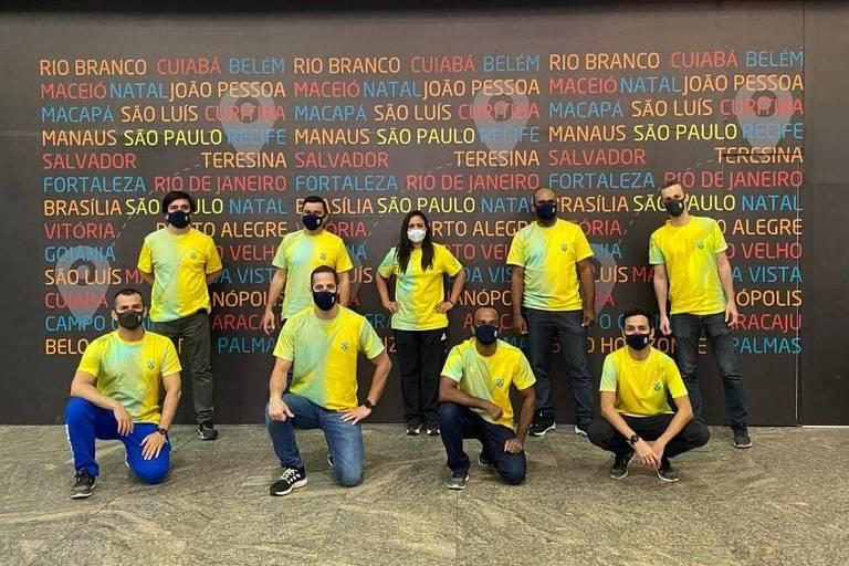 Dez pessoas com camisetas amarelas e verdes posam para foto em frente a painel no aeroporto