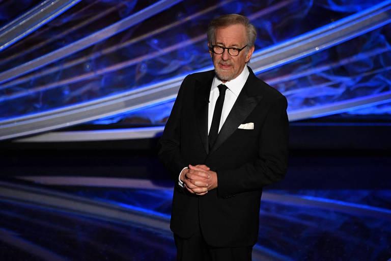 Homem branco de roupa de gala fala em palco
