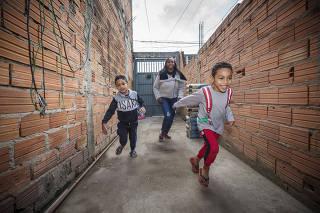 Brincar na Pandemia:  Irmaos Gustavo (esq) e Felipe  Silva Scardova, ambos de 5 anos,  ao lado da mae Priscila Santos da Silva,26, brincam no quintal de casa no Jardim Pantanal.  Pesquisa