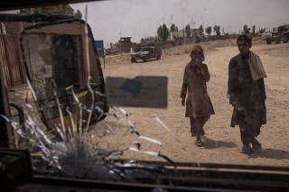 Boys walk past a damaged Humvee near the front line in Lashkar Gah, Afghanistan on May 10, 2021. (Jim Huylebroek/The New York Times)