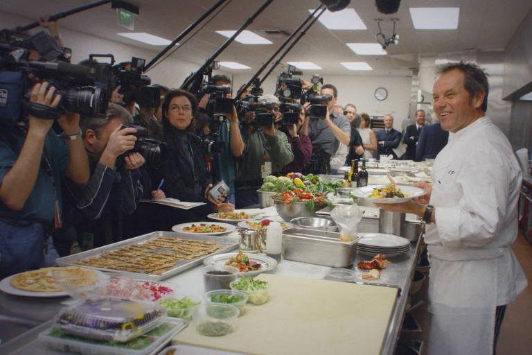 Chef austríaco Wolfgang Puck por trás de uma mesa extensa. Do outro lado estão diversos jornalistas com câmeras e microfones