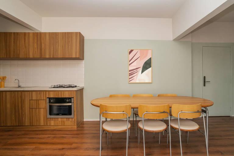 Sala com mesa com seis cadeiras e cozinha ao lado