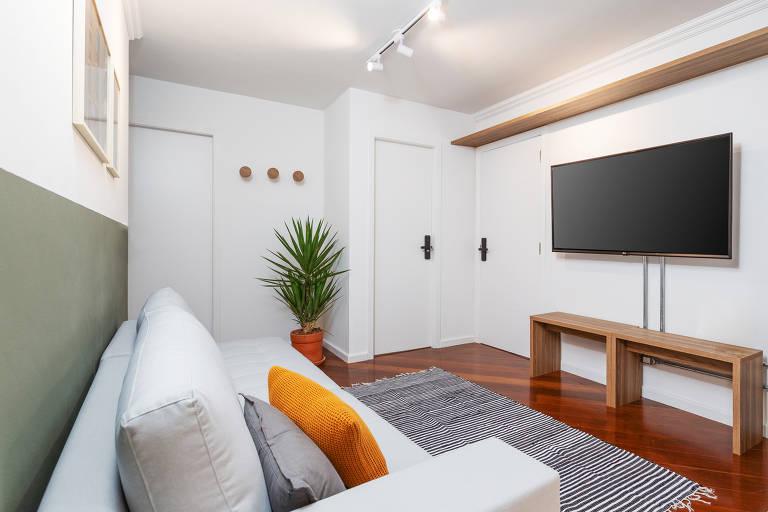 Sala de apartamento, com sofá e tevê