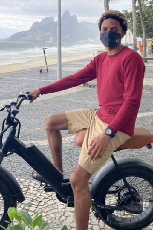 Homem negro em sua bicicleta com praia ao fundo