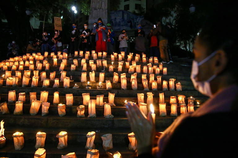 Com velas acesas, pessoas participam no largo da Memória, em São Paulo, de cerimônia em homenagem às 500 mil pessoas que morreram em decorrência do coronavírus