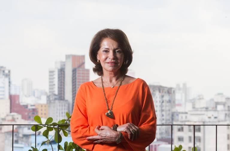 Maria Helena Guimarães aparece sorrindo e de braços cruzados na sacada de um prédio. Ao fundo, a cidade de São Paulo.