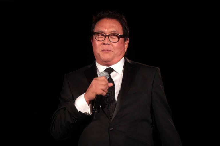 Homem de terno preto e óculos discursa em evento
