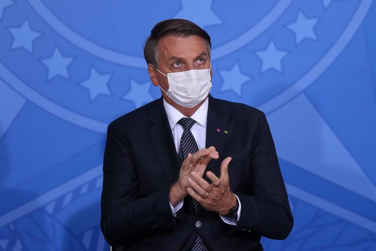 O presidente Jair Bolsonaro está sentado de terno, máscara e fazendo o gesto de aplaudir algo