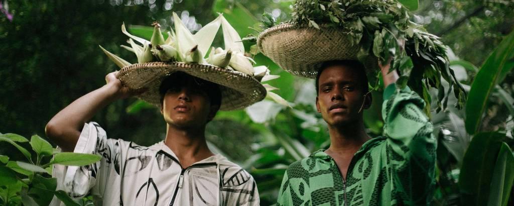 Dois homens (um negro e um indígena) carregam cesta de alimentos em suas cabeças
