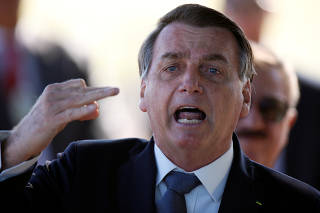 Brazil's President Jair Bolsonaro reacts as he leaves Alvorada Palace, amid the coronavirus disease (COVID-19) outbreak in Brasilia