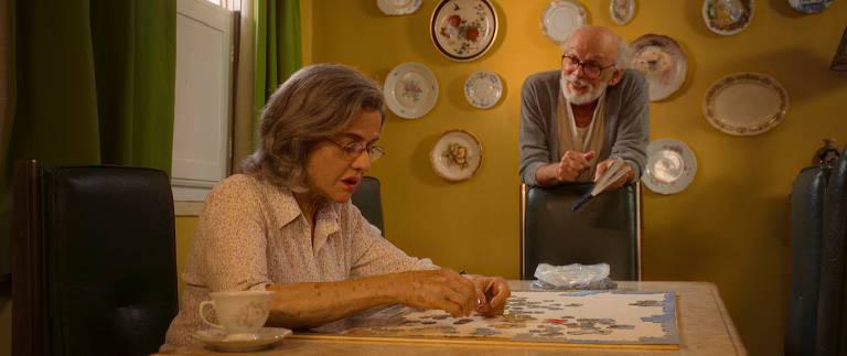 mulher branca idosa faz quebra cabeça em mesa enquanto homem branco idoso apoiado no encosto de uma cadeira a observa