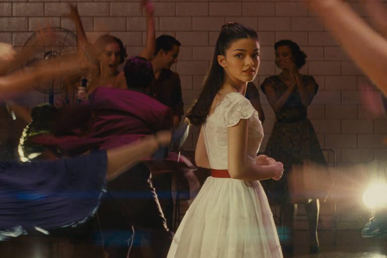Jovem moça morena de cabelos lisos usa vestido branco em baile nos anos 1960