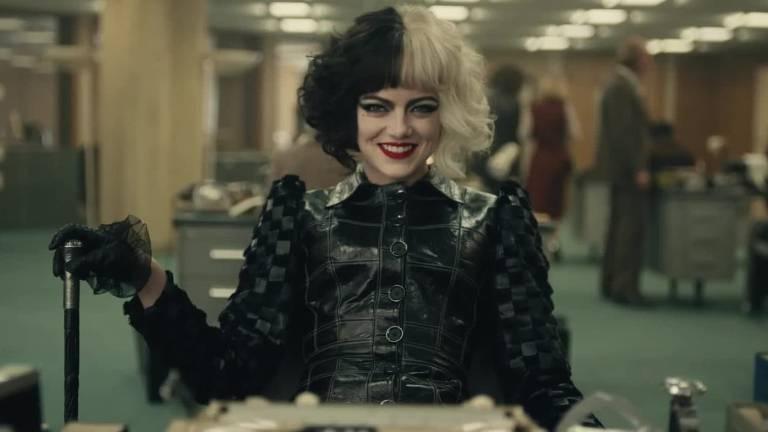 Mulher de roupas pretas e cabelo preto e branco sorri sentada