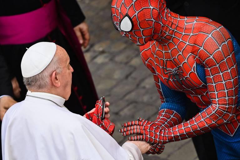 Papa, de branco, aperta mão de pessoa fantasiada de Homem-Aranha
