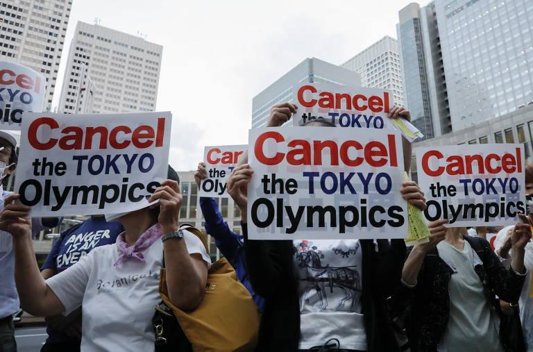 Pessoas ocupam rua e seguram cartazes onde pedem cancelamento dos jogos de Tóquio