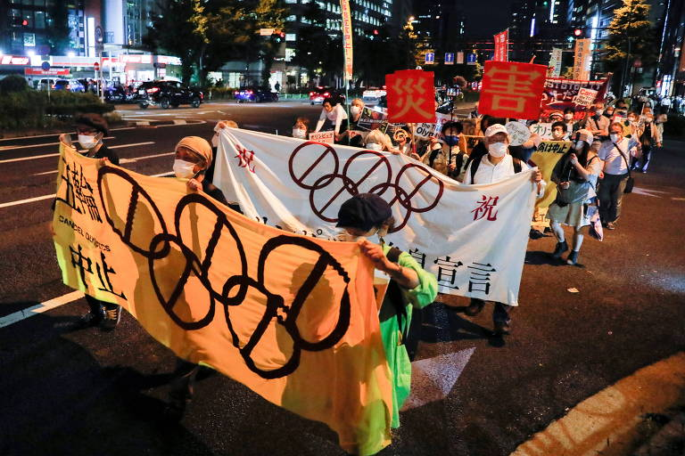 Manifestantes carregam faixas e fazem protesto nas ruas de Tóquio contra a realização da Olimpíada