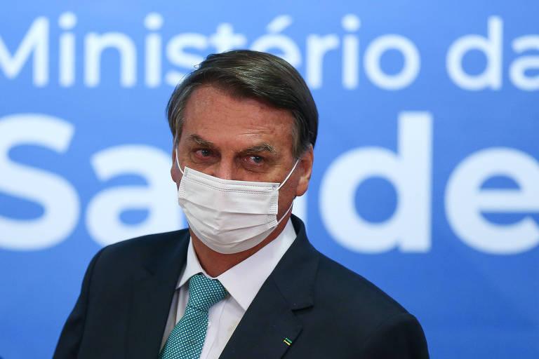 """Bolsonaro usando máscara diante de um painel onde se lê """"Ministério da Saúde"""""""