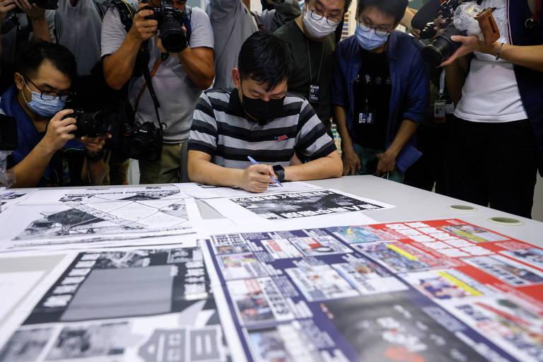Cercado por fotógrafos, o editor-executivo do Apple Daily, Lam Man-chung, analisa a última edição da publicação