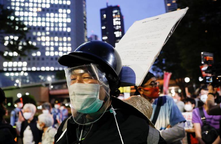 Manifestante com máscara e face shield protesta contra Olimpíada de Tóquio