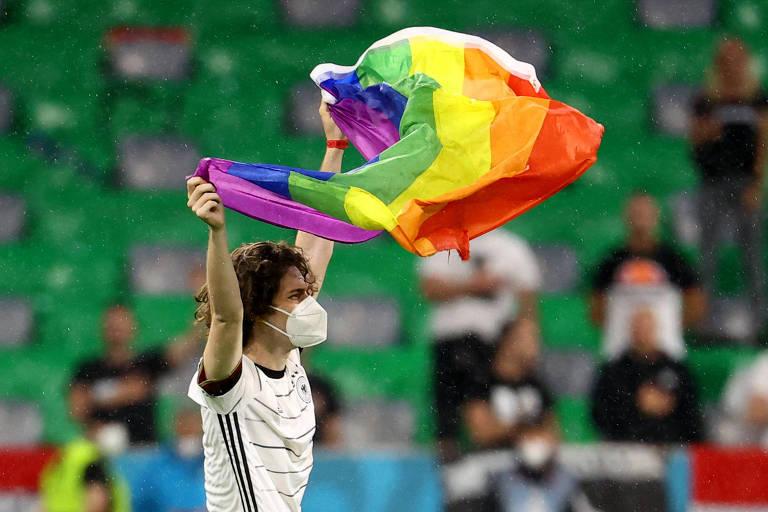 Torcedor invade o gramado da Allianz Arena com uma bandeira com as cores do arco-íris
