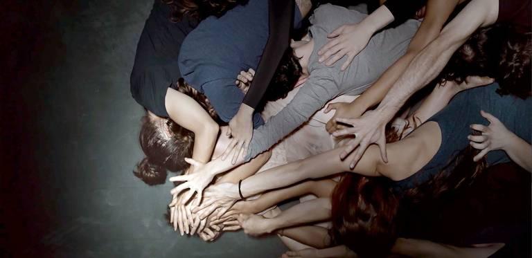 Diversas pessoas com os braços estendidos estão empilhados no chão