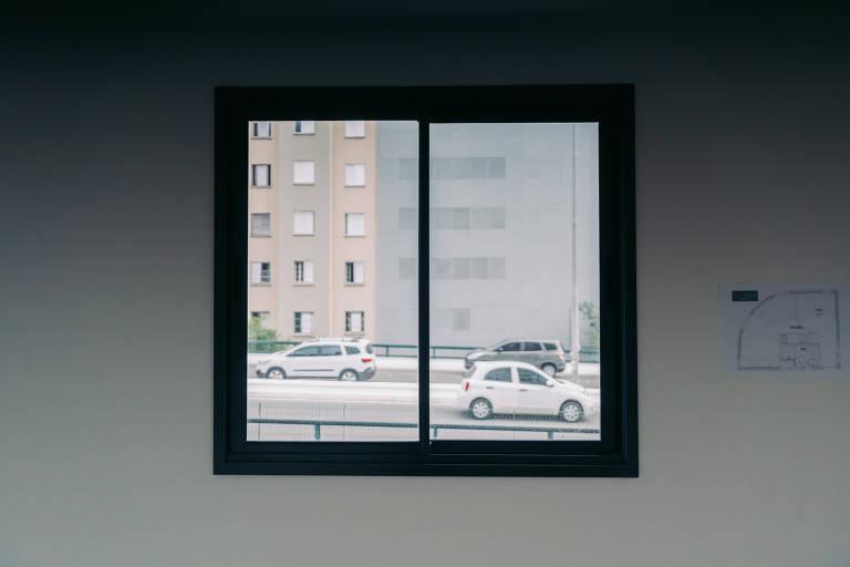 Dois carros passando, vistos por janela