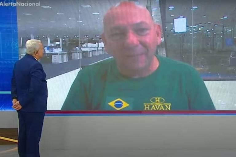 Apresentador fala em telão com homem de camiseta
