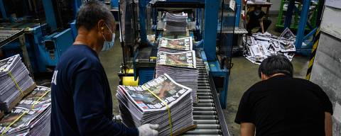 Apple Daily employees work in the printing room as the last edition of the newspaper is printed in Hong Kong early on June 24, 2021. - The 26-year-old tabloid announced closure the previous day after having its assets frozen by the police. (Photo by Anthony WALLACE / AFP)