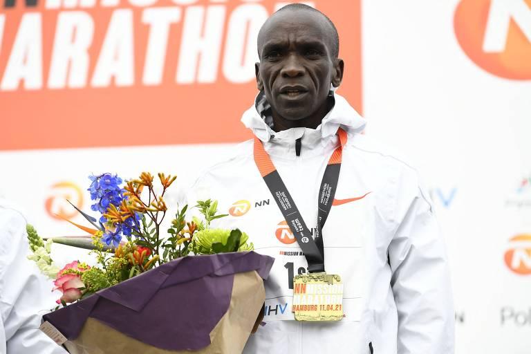 Eliud Kipchoge posa no pódio com um buquê de flores e a medalha de ouro da Maratona de Twente, na Holanda