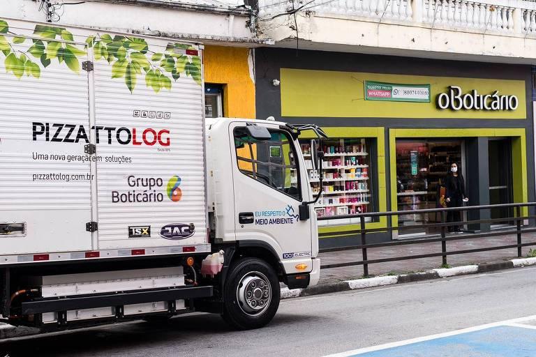 Caminhão branco passando na porta de uma loja da Boticário