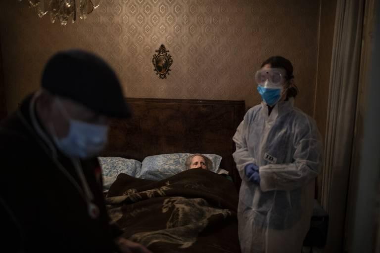 Josefa Ribas, que está acamada, olha para a enfermeira, enquanto o marido de Ribas, José Marcos, está de pé em sua casa em Barcelona.