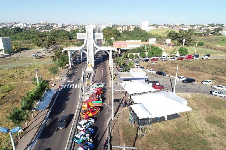 Imagem mostra veículos ligados à Saúde e ao Corpo de bombeiros estacionados, com tendas à direita