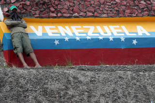 FILE PHOTO: Demonstrator rests on the border sign welcoming to Venezuela