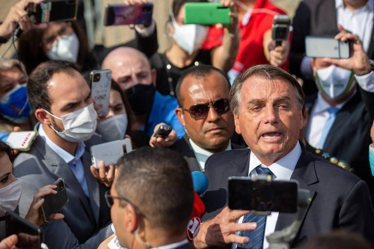 Jair Bolsonaro está cercado por vários homens; vários estão segurando o celular para filmar ou fotografar o presidente, que está sem máscara (além dele, há outros homens sem máscara na foto)