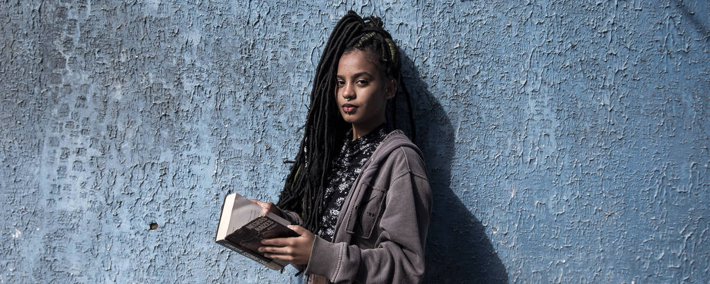 Bruna Jesus Santos, 17, negra e com tranças longas, segura livro em Cidade Tiradentes, na periferia de SP; ela quer cursar direito ou ciências humanas