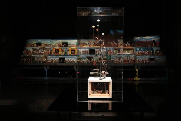 Em caixa de vidro, obra com circunferências tridimensionais suspensas em hastes de metal