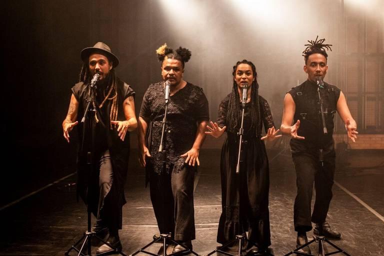 Em um palco, quatro negros, três homens e uma mulher, vestidos de preto declamam poesias