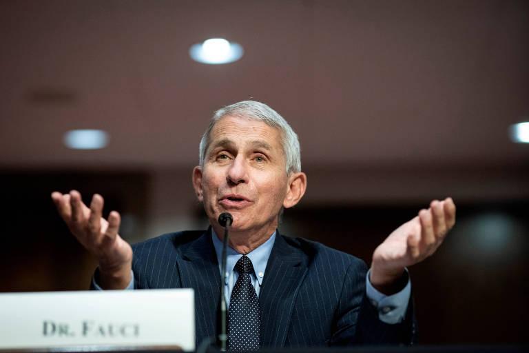 """O virologista Anthony Fauci é branco e tem cabelo curto grisalho. Ele está de paletó escuro e gesticula abrindo as duas mãos para cima em frente a microfone. Em frente a ele há uma placa com seu nome, """" Dr. Fauci"""""""
