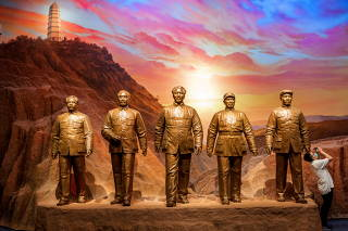 A man takes pictures next to statues of former Chinese Communist leaders at the Museum of the Communist Party of China that was opened ahead of the 100th founding anniversary of the Party in Beijing