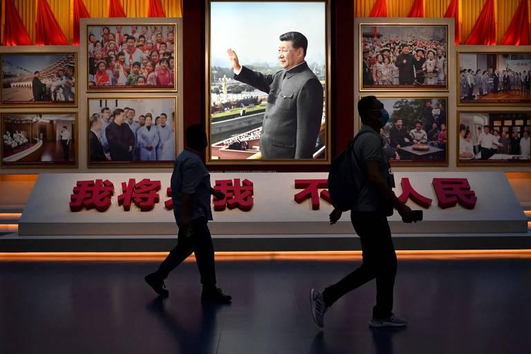Homens passam em frente a imagem do atual dirigente da China, Xi Jinping, no museu dedicado ao Partido Comunista, em Pequim