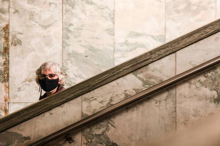 Paredes de mármore e dois corrimões de mármores, com a cabeça de uma mulher branca, de cabelos grisalhos, máscara de proteção e óculos aparecendo entre o corrimão e uma das paredes