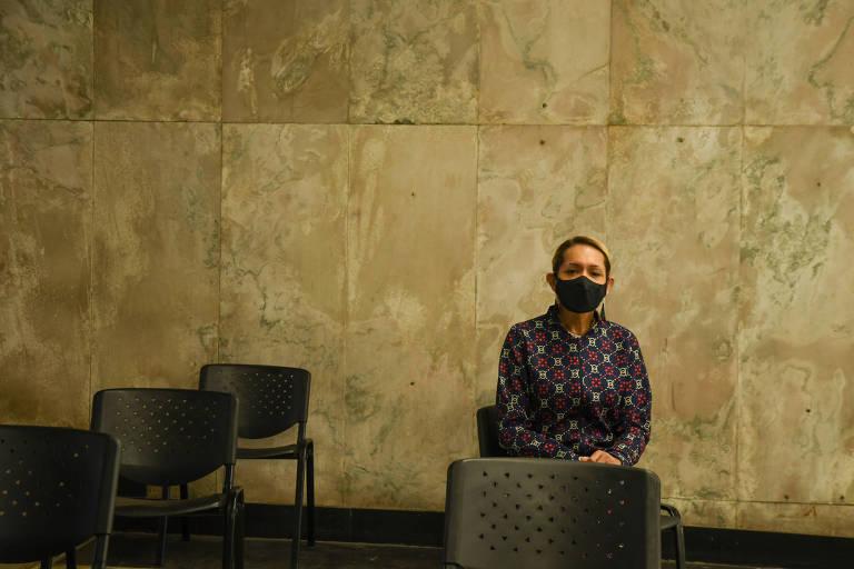 Uma parede de mármore ao fundo com cadeiras pretas enfileiradas na frente. Em uma das cadeiras, no canto direito da foto, uma mulher transexual loira, de máscara de proteção preta e uma blusa de frio azul escura com desenhos cor de rosa