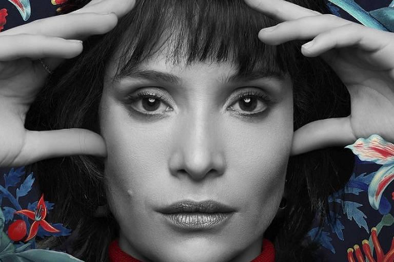Close no rosto da atriz em preto branco, rodeada de flores e plantas em tons de azul e vermelho