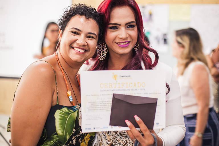 duas mulheres seguram diploma