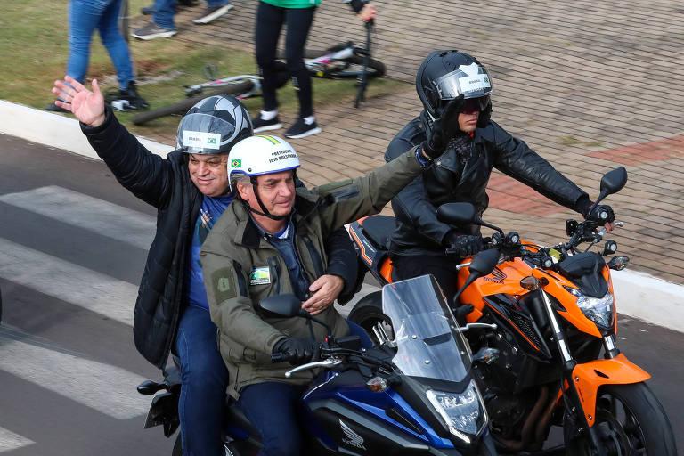Bolsonaro dirige uma moto e acena