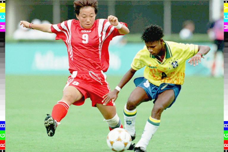 Mulher de vermelho e mulher de amarelo disputam bola em gramado