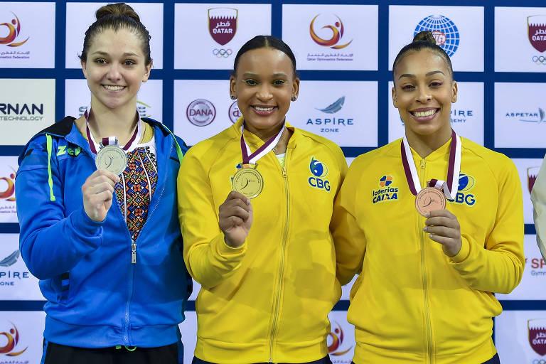Três atletas mostram suas medalhas no pódio